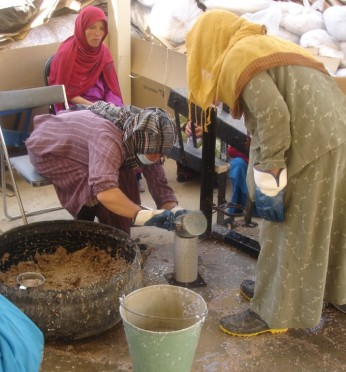 Making fuel briquettes: Women at the ARZU Center pouring briquette mixture into mold for the press; 7-7-10.